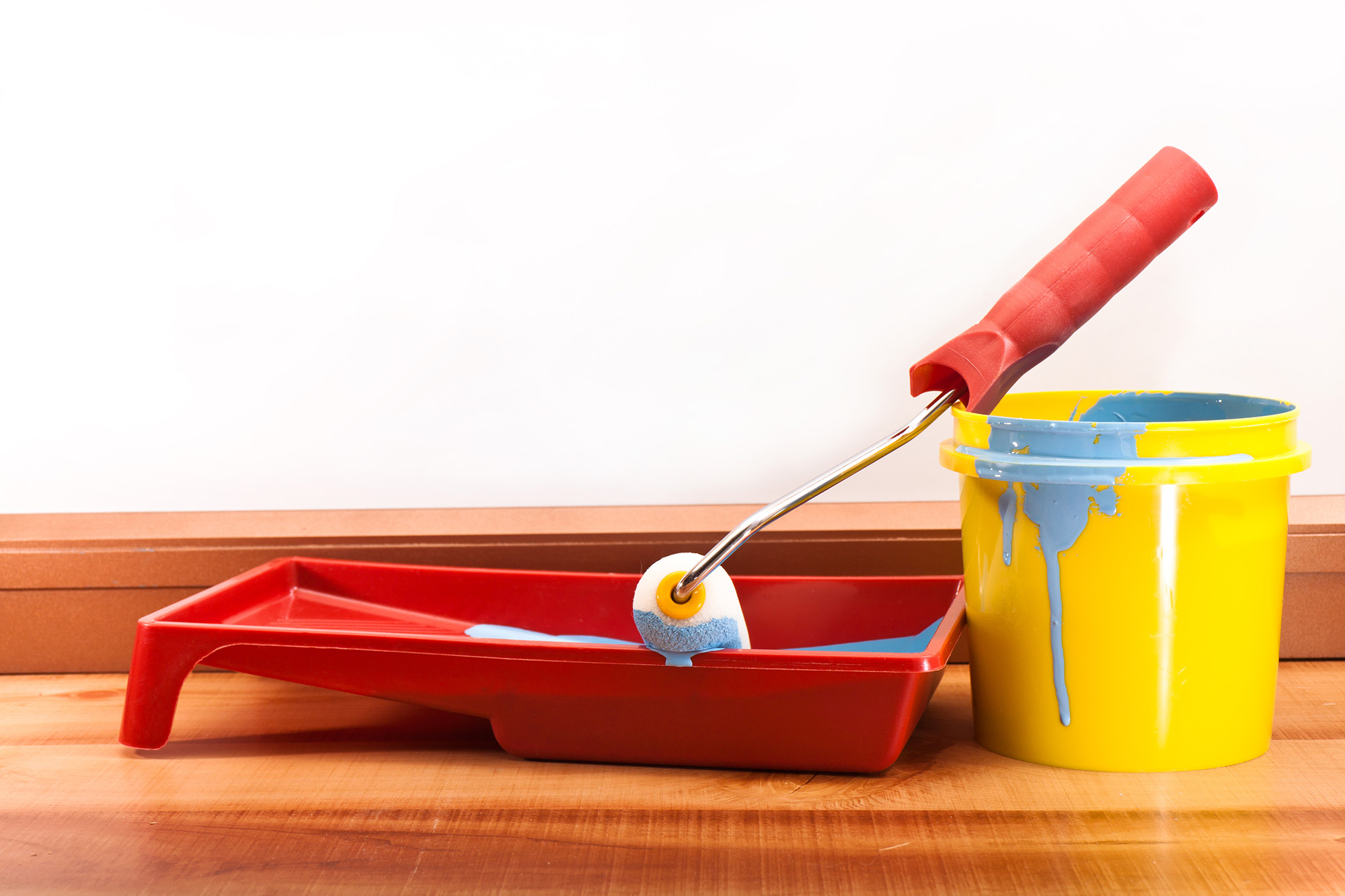 Yellow bucket of blue paint and a roller for painting walls